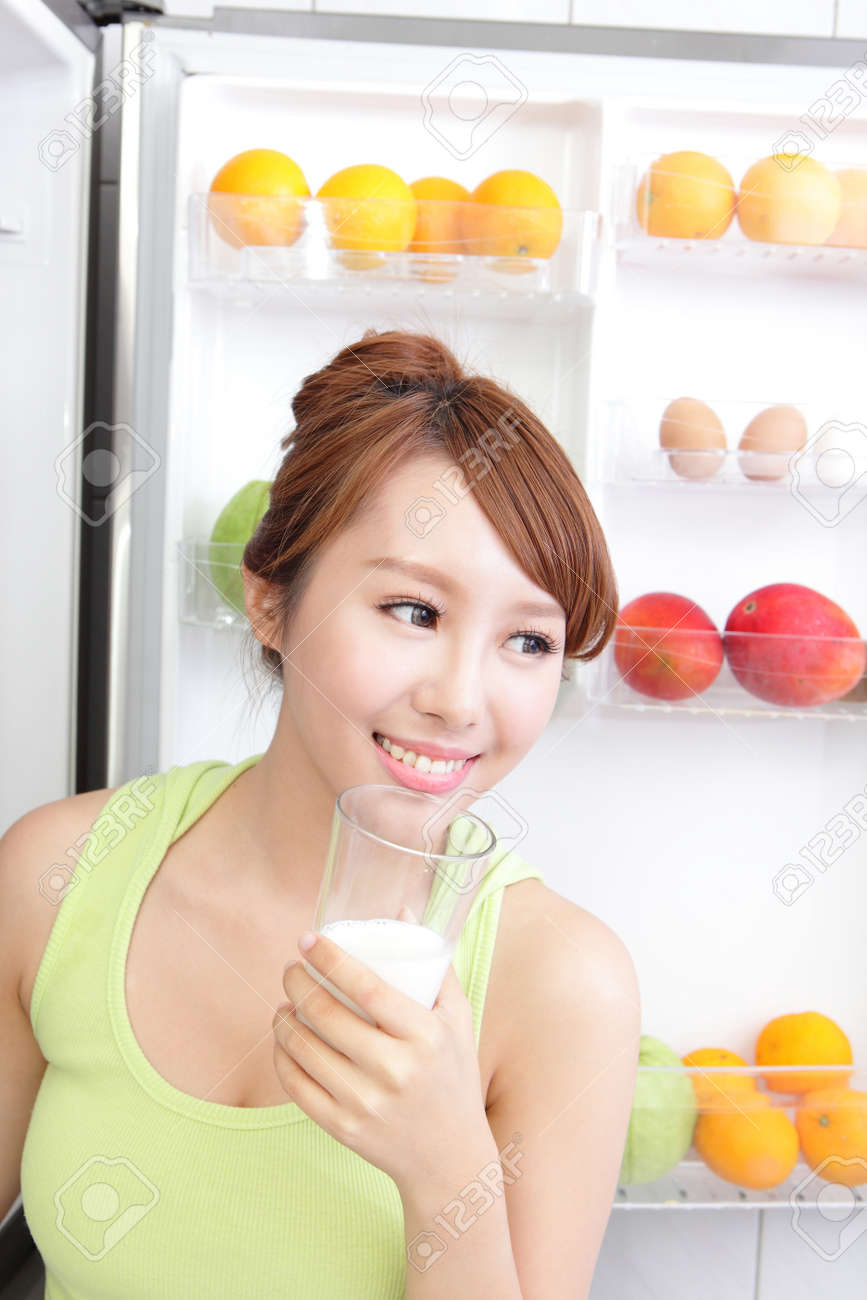 Healthy Eating Concept .Diet. Beautiful Young Woman drink milk near the Refrigerator. Fruits and Vegetables, asian model Stock Photo - 22701479
