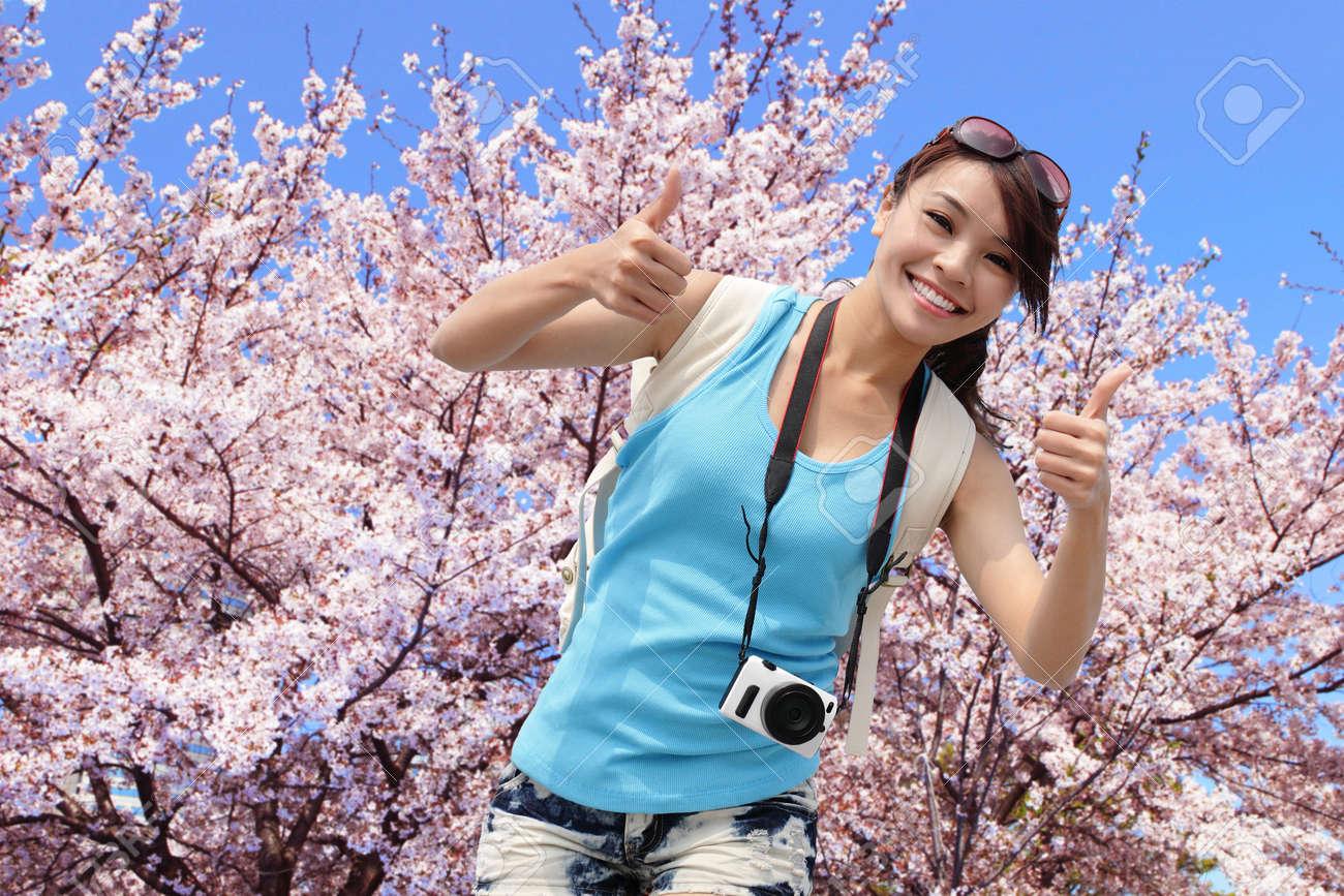 Happy Woman Traveler Show Thumb Up With Sakura Tree On Vacation - Vacation in japan