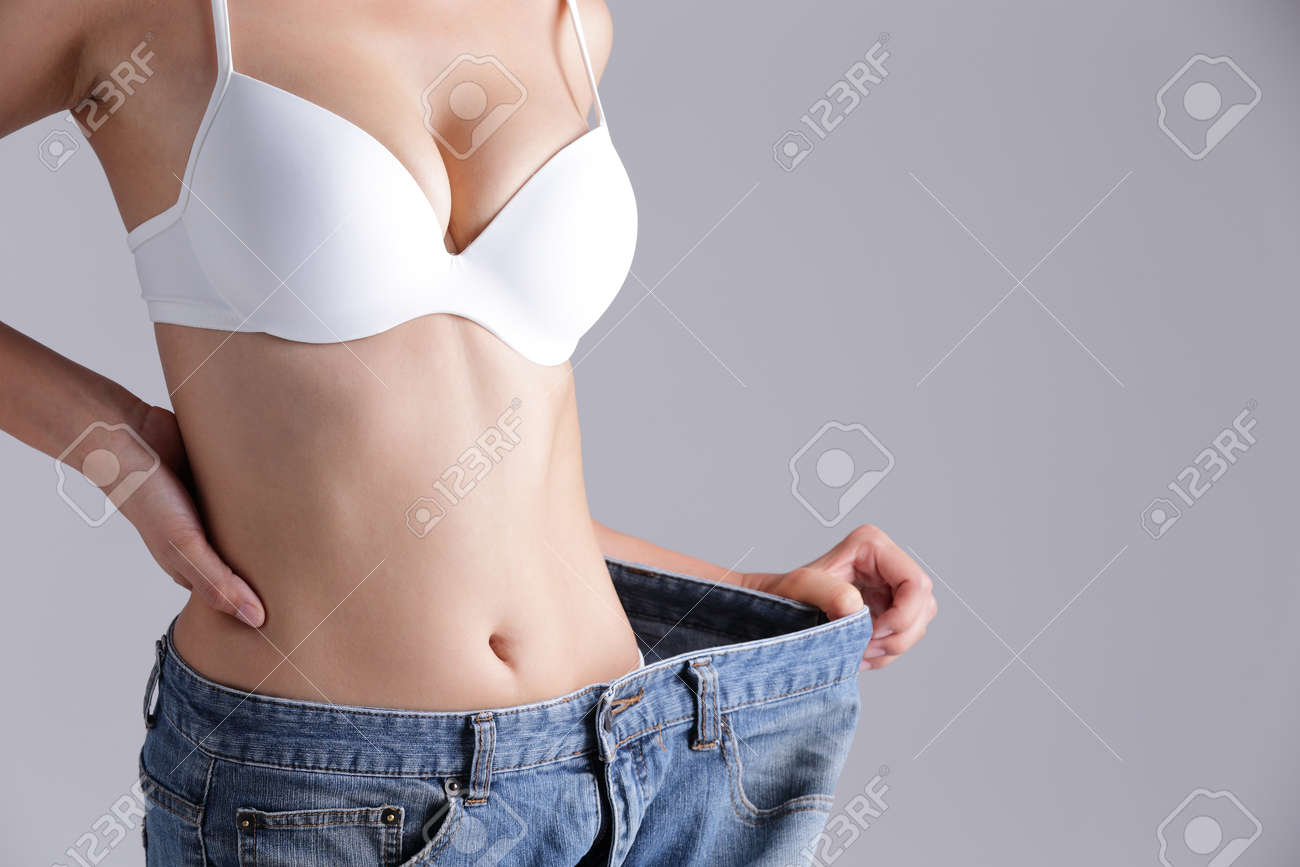 woman shows weight loss by wearing old jeans, asian beauty - 40856636