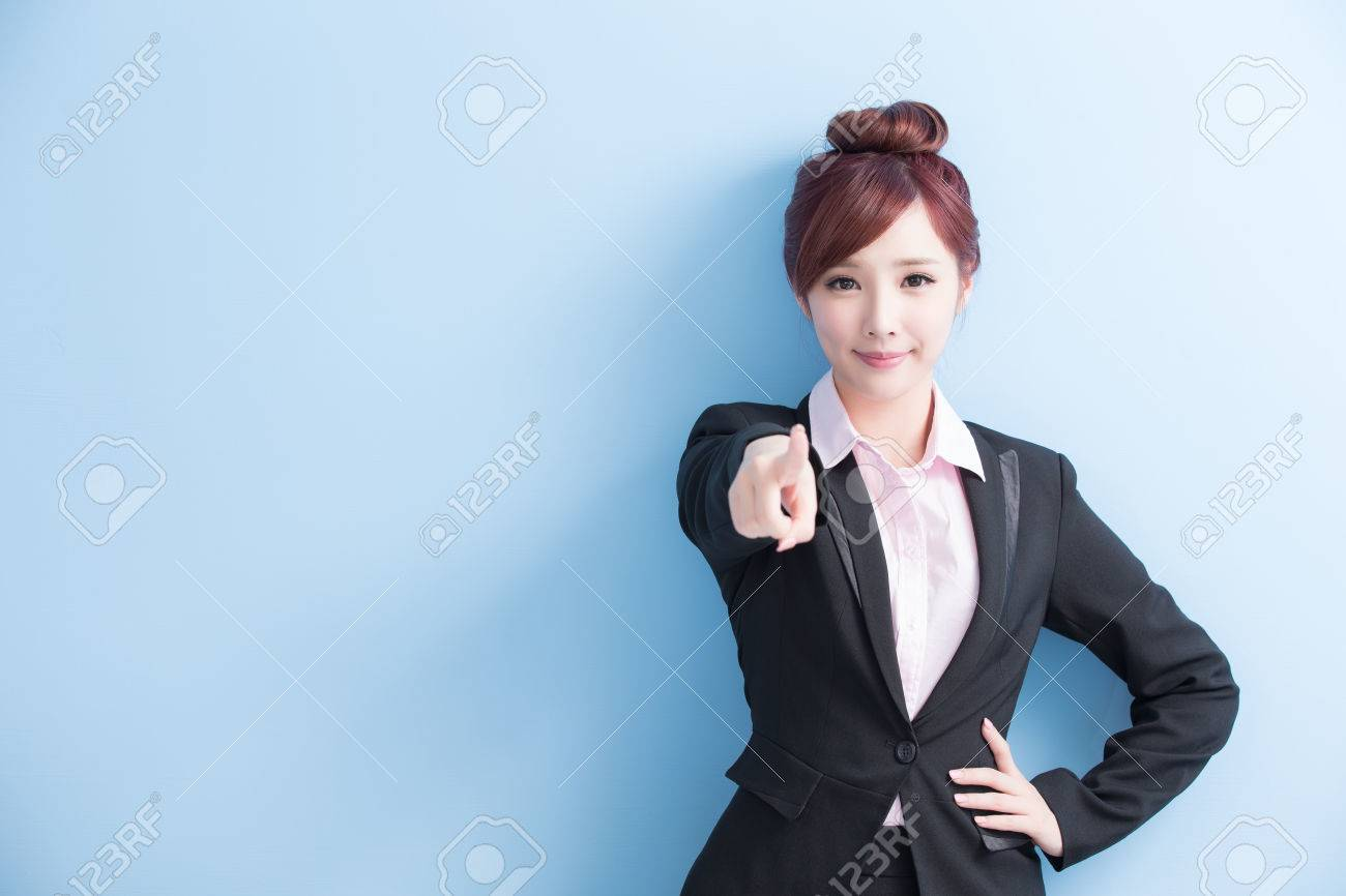 business woman is smile and pointing to you isolated on blue background, asian - 65007337