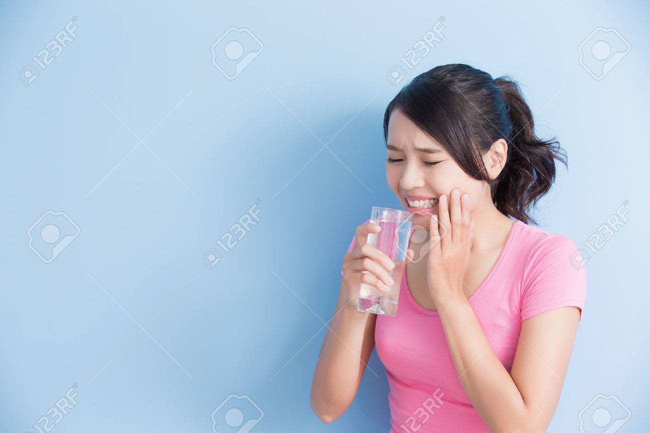 woman drink water with sensitive teeth isolated on bluebackground - 65012946