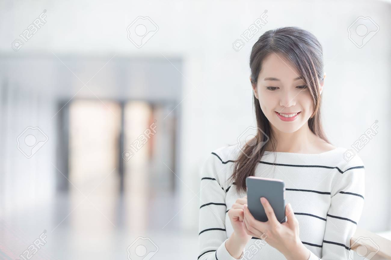 beauty woman use phone and smile happily in hongkong Standard-Bild - 65441583