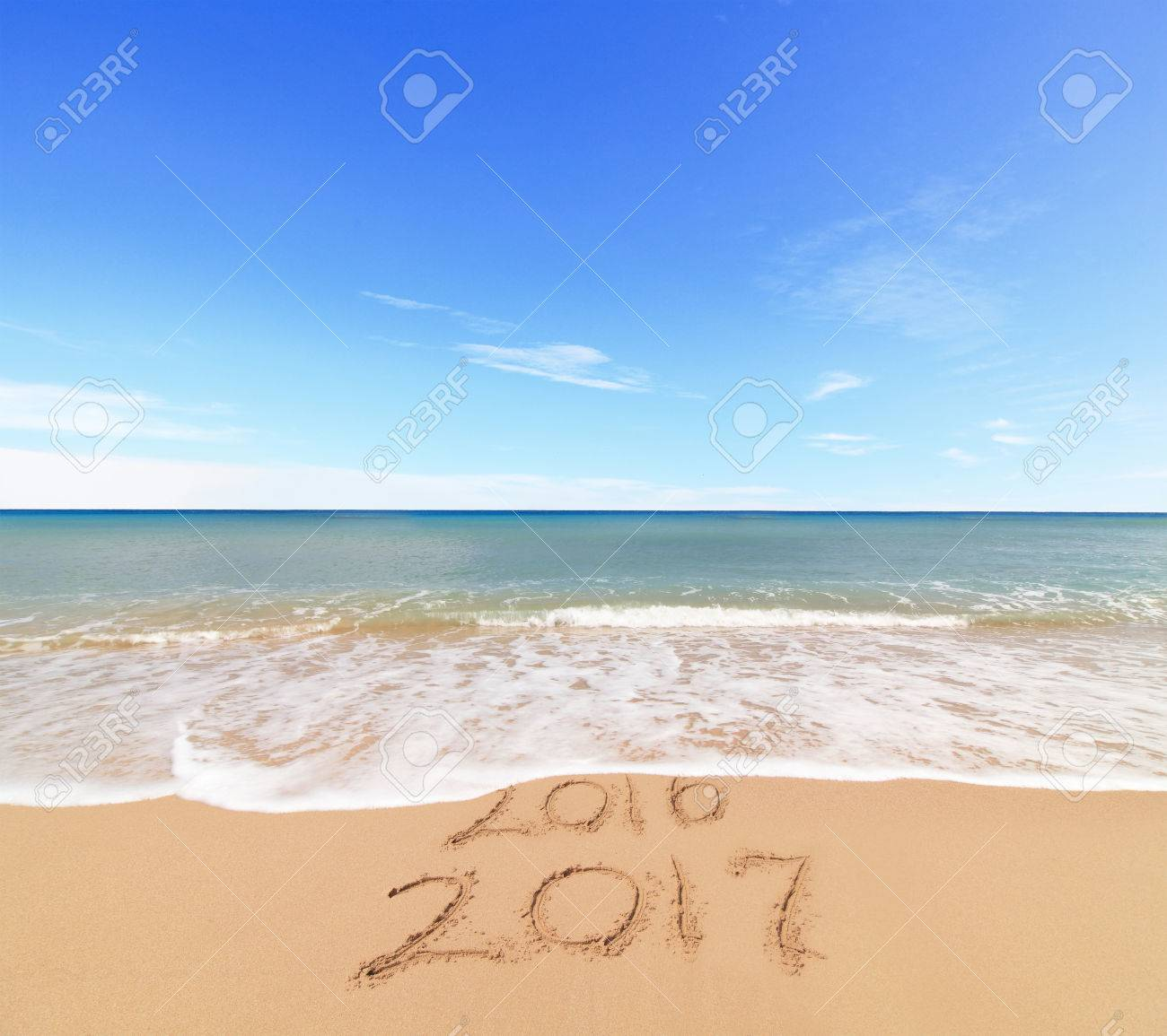 New Year 2017 is coming concept - inscription 2017 and 2016 on a beach sand, the wave is covering digits 2016 Standard-Bild - 65442124