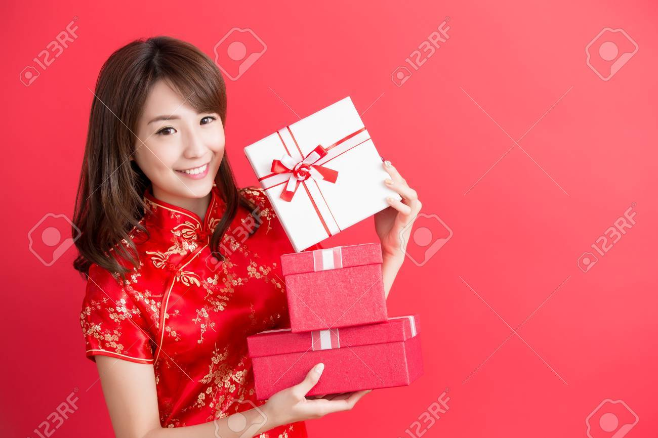 beauty woman wear cheongsam and show gift box to you in chinese new year Standard-Bild - 69806780