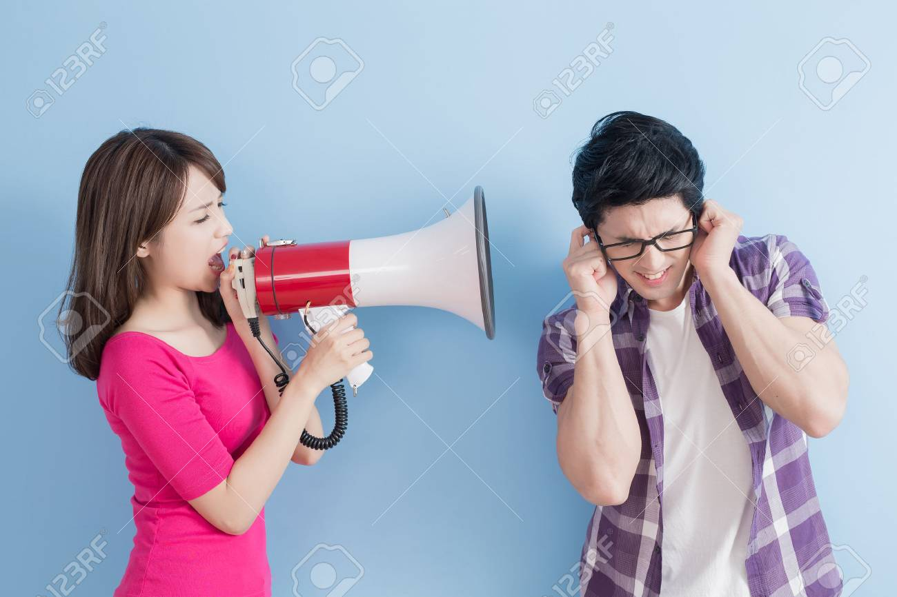 woman take the microphone shout to man angrily isolated on blue background Standard-Bild - 70046704