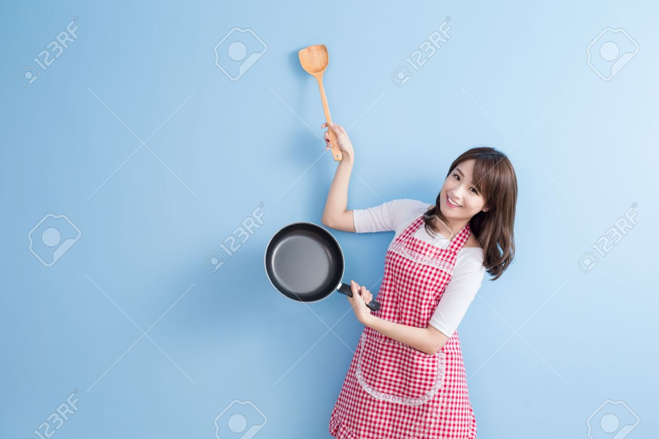 beauty housewife take wok and rice spoon isolated on blue background Standard-Bild - 70046722