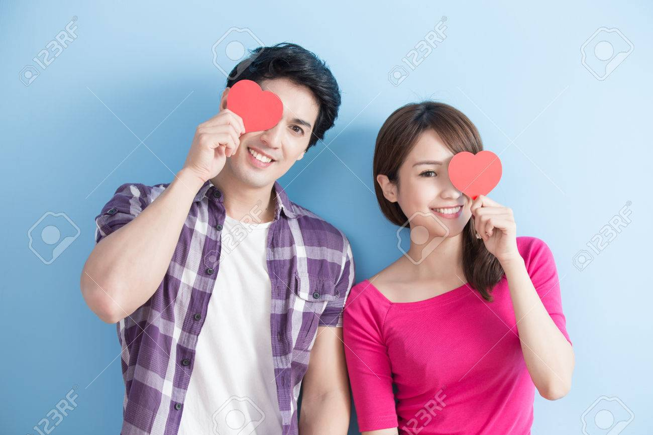 Attractive young couple holding red love hearts over eyes isolated on blue background Standard-Bild - 71249437