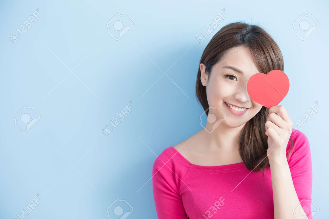 Attractive young woman holding red love hearts over eyes isolated on blue background Standard-Bild - 71232980