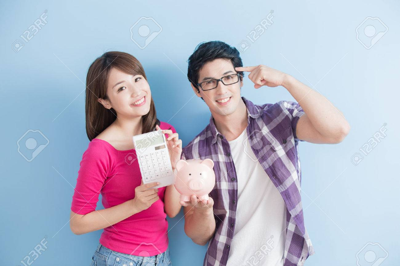 young couple hold pink pig bank and calculator isolated on blue background Standard-Bild - 71785017