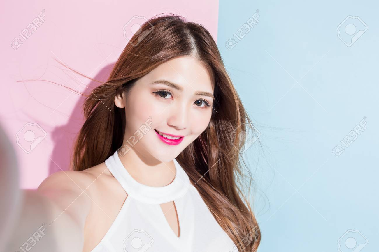 Close-up photo of a pretty girl making selfie photo on smar tphone isolated on pink and blue background. - 106975368