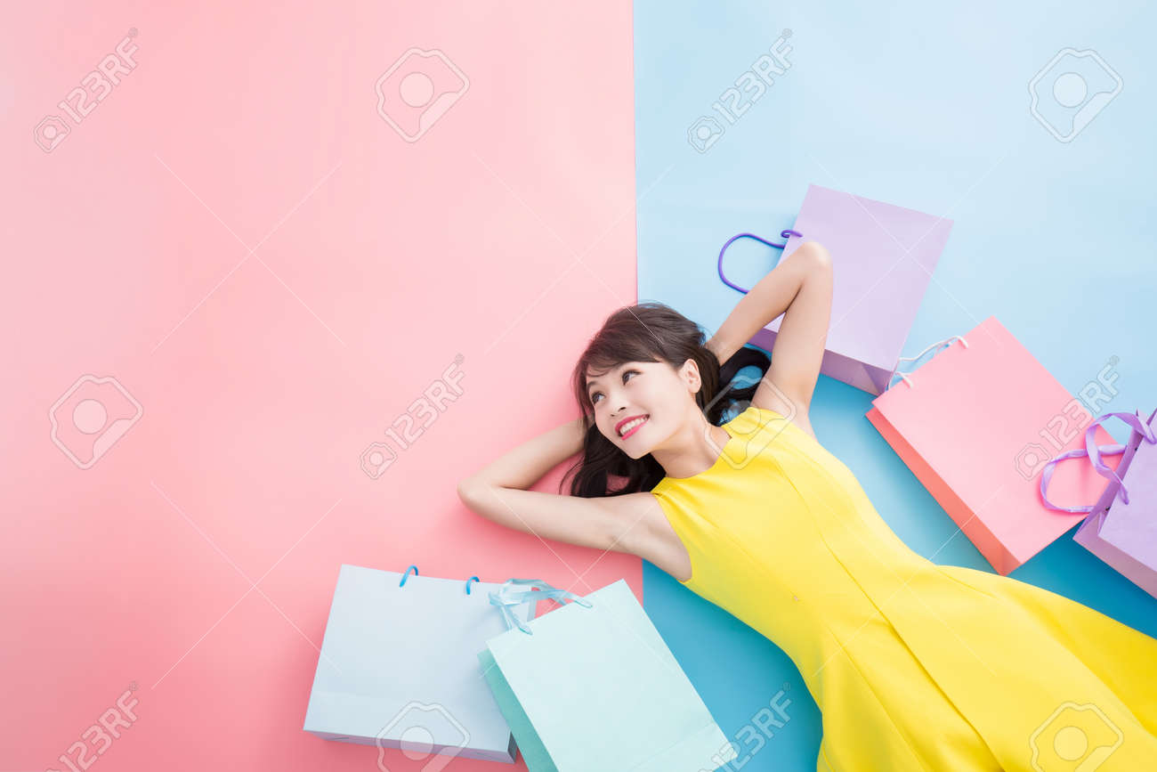woman take shopping bag happily and look copy space on the blue and pink background - 108677580