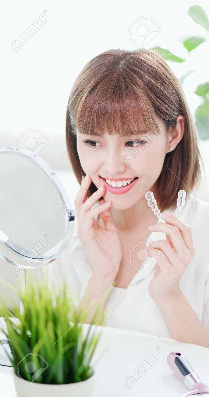 Beauty woman look her beautiful teeth in the mirror happily after take off the invisible brace - 114975676