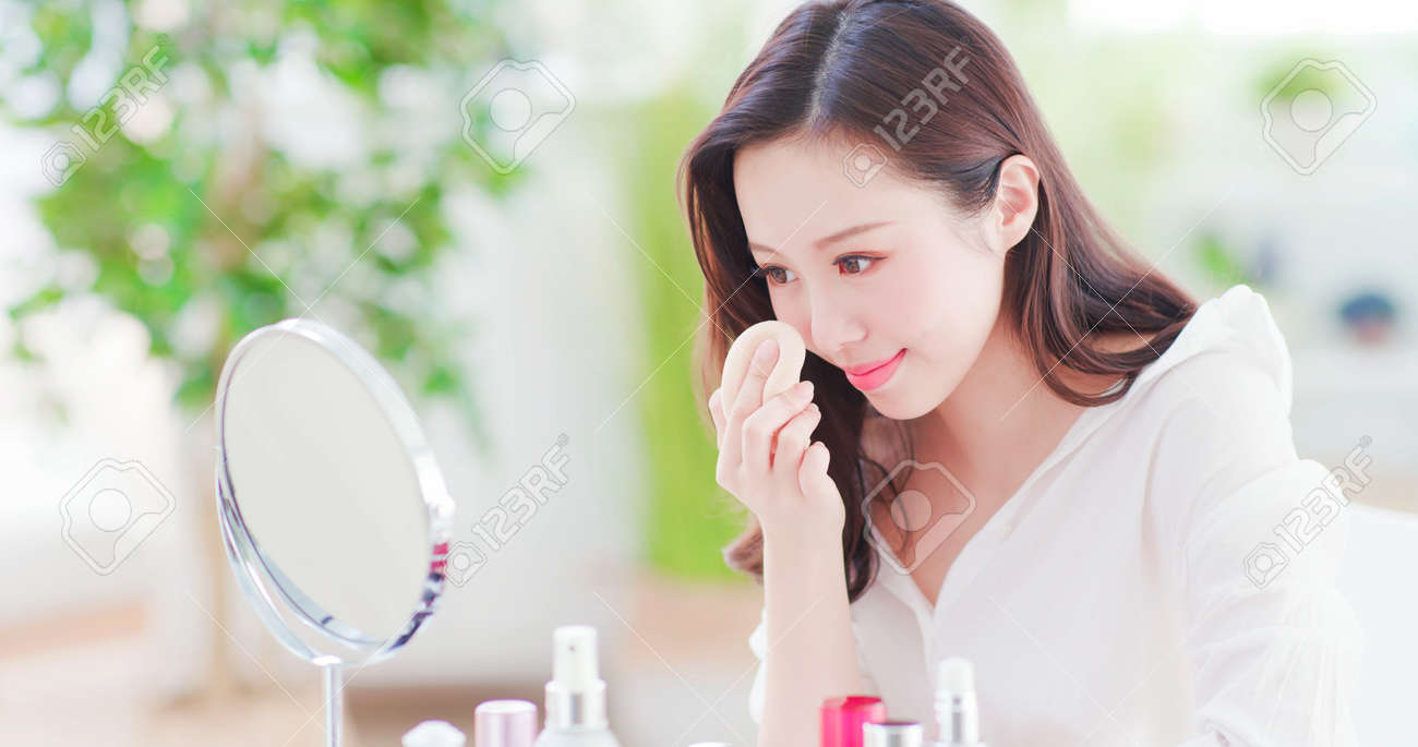 Beautiful asian woman using cosmetic sponge on face and look mirror at home - 116601462