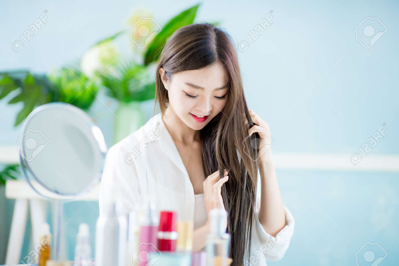 Beautiful asian woman applying oil onto hair with mirror at home - 119967505