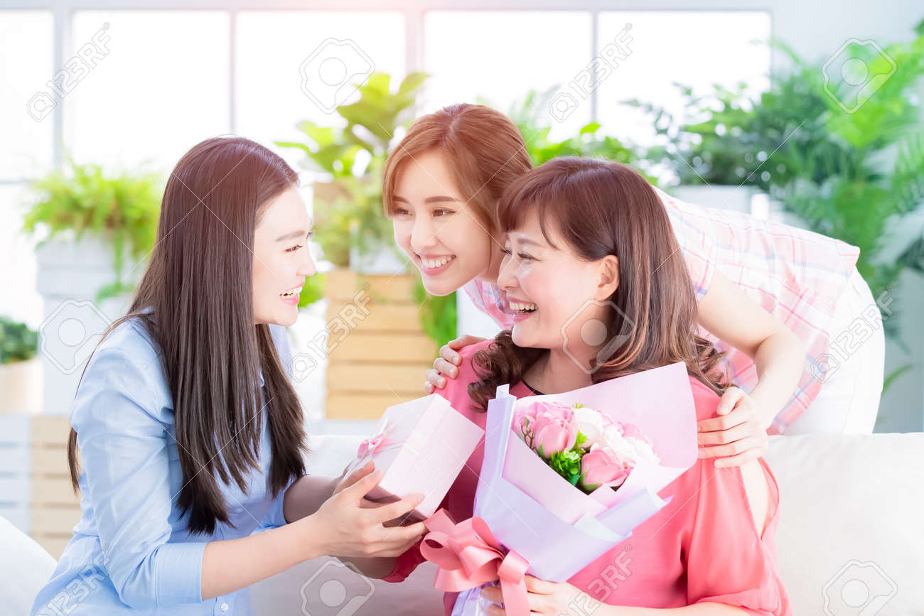 Happy mother day - two daughters give flowers and gift to her mom at home - 121259733
