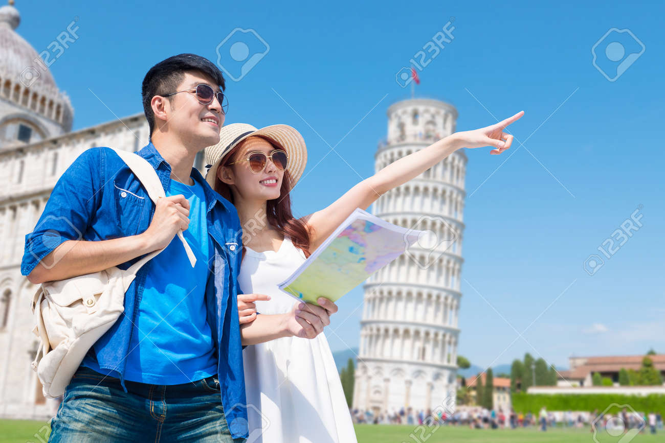 couple take world map when visiting leaning tower of Pisa in Italy - 121836365
