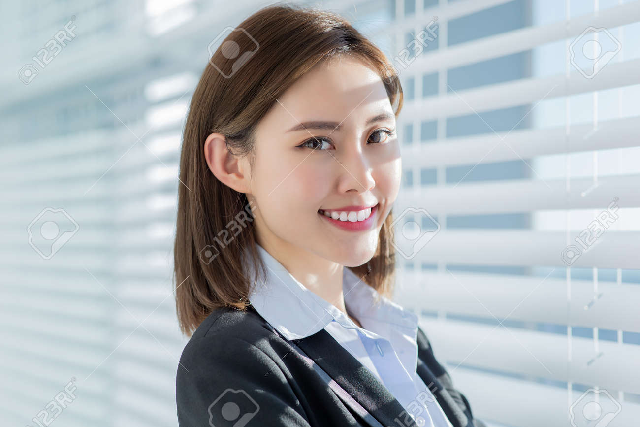 Asian business woman smile at you with confidence by the curtain in the office - 125774771