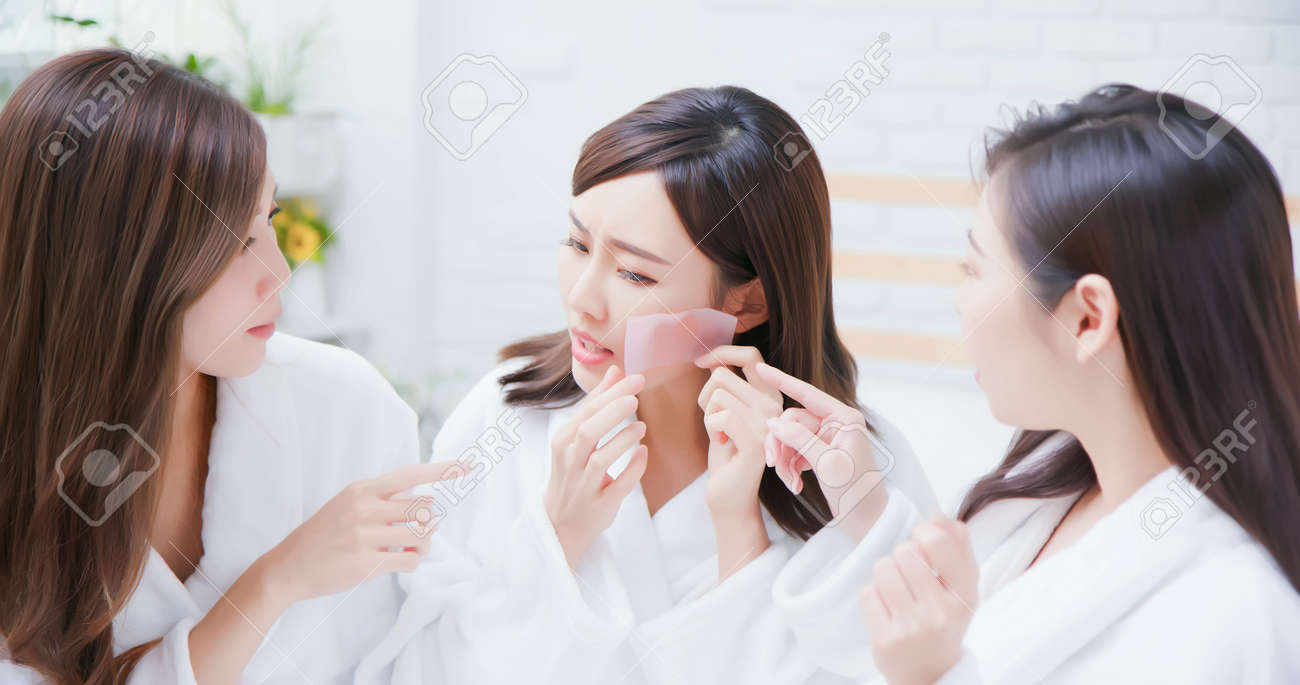 asian women put the oil absorbing paper on her face and feel bad - 128419463