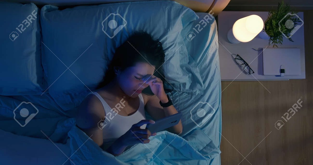 High angle view shot of asian woman has eye pain and feel tired because watching smartphone in dark at night - 134841952