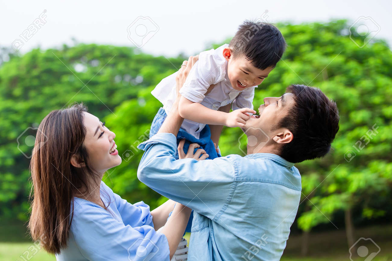 Father hold boy in his arm and parents play with kid outdoor - 140507483