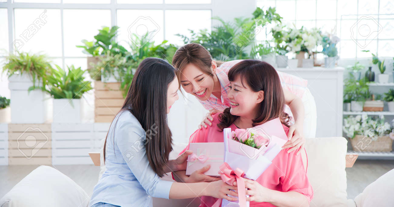two daughters give flowers to her mom and celebrate happy mother day at home - 143119069