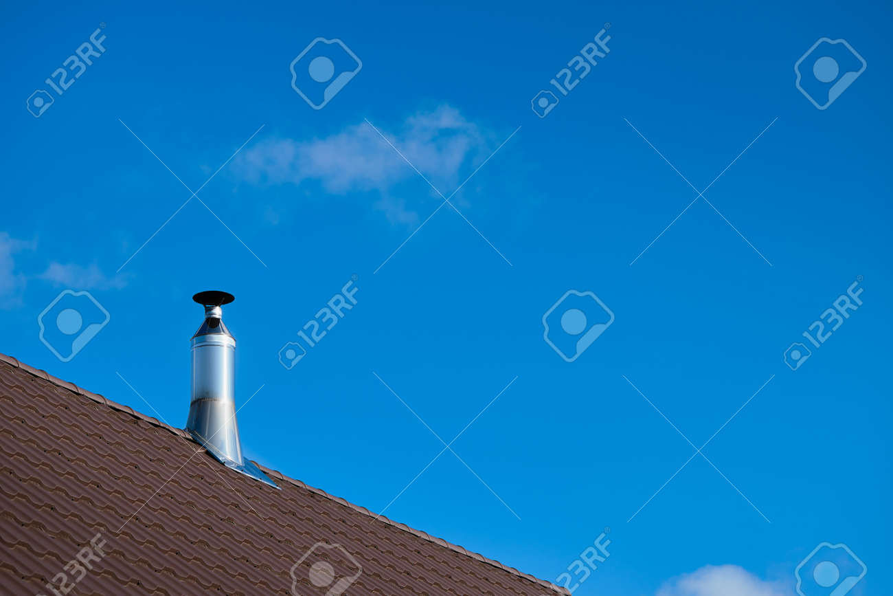 Modern style chimney from oven or fireplace stacked stainless steel on tiled roof made according to fire safety requirements, and to avoid condensation when reaching dew point in flue gases. - 146538106