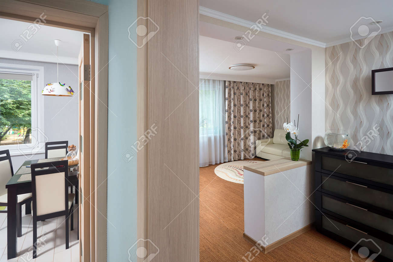 View from the hallway to the open doors to the kitchen and a room in a studio apartment. Doorway with wooden interior door with glass inserts in loft style closeup horizontal. - 158289861