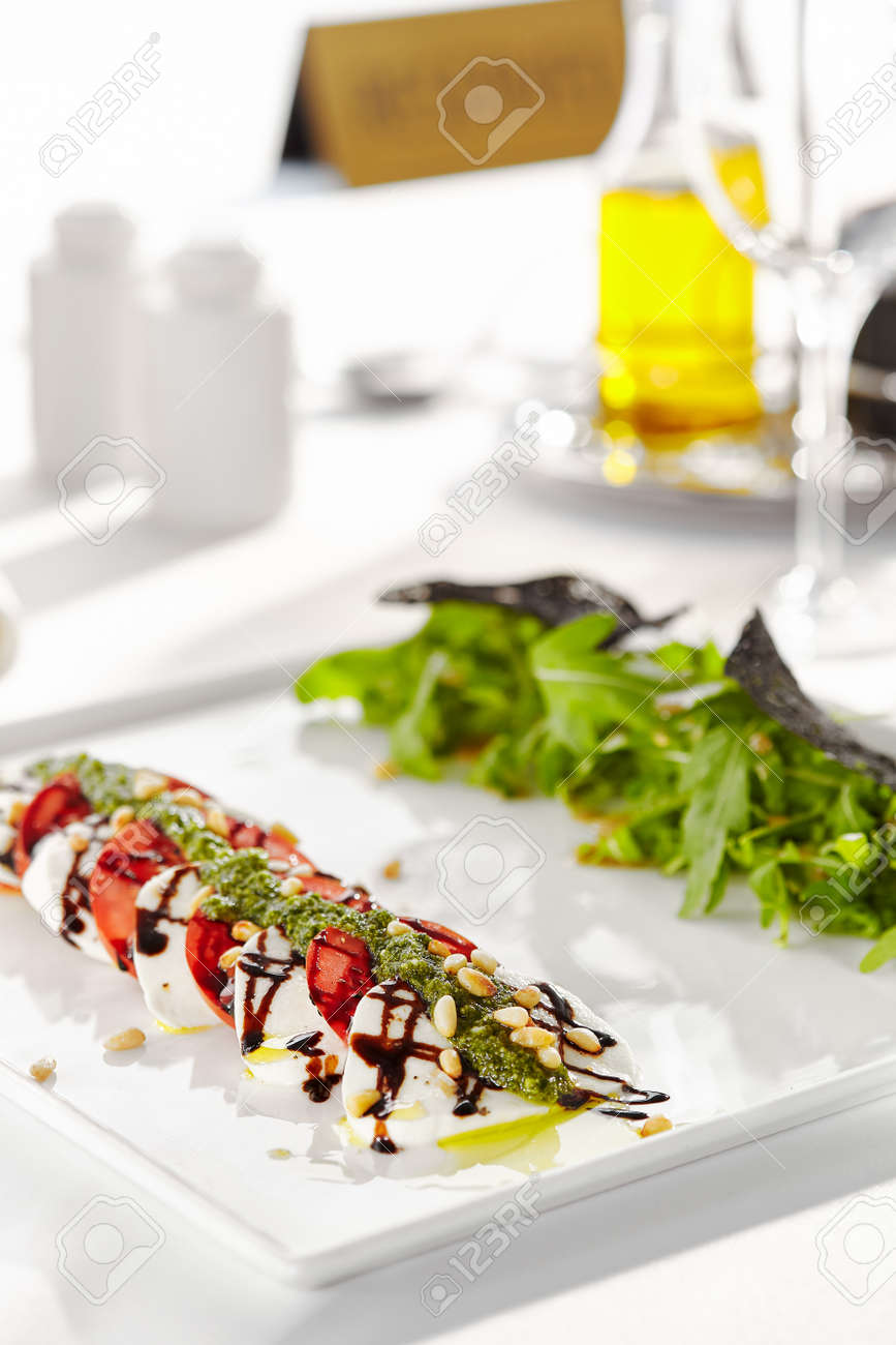 Gourmet, restaurant, delicious dinner food - close up of Caprese Salad. Salad with Tomatoes, Mozzarella Cheese, Balsamic. Salad Dressing with Pesto Sauce and Rocket Salad - 131432612