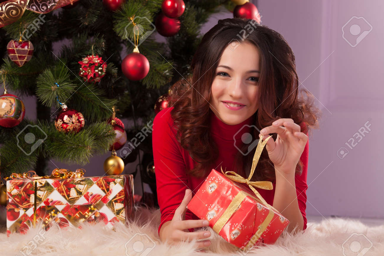 Beautiful girl with a gift near the Christmas tree Stock Photo - 23667143