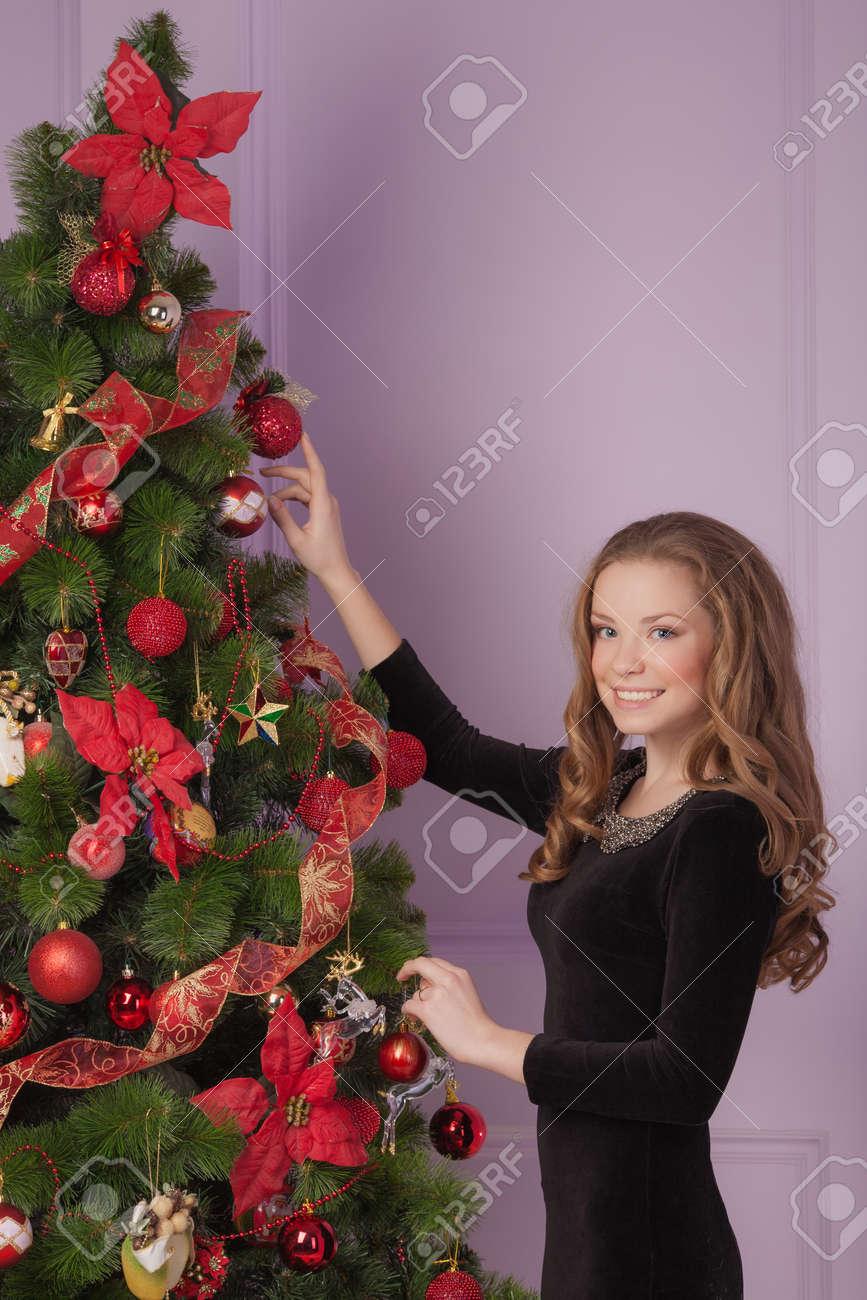 Beautiful girl hanging toy on Christmas tree Stock Photo - 23665915