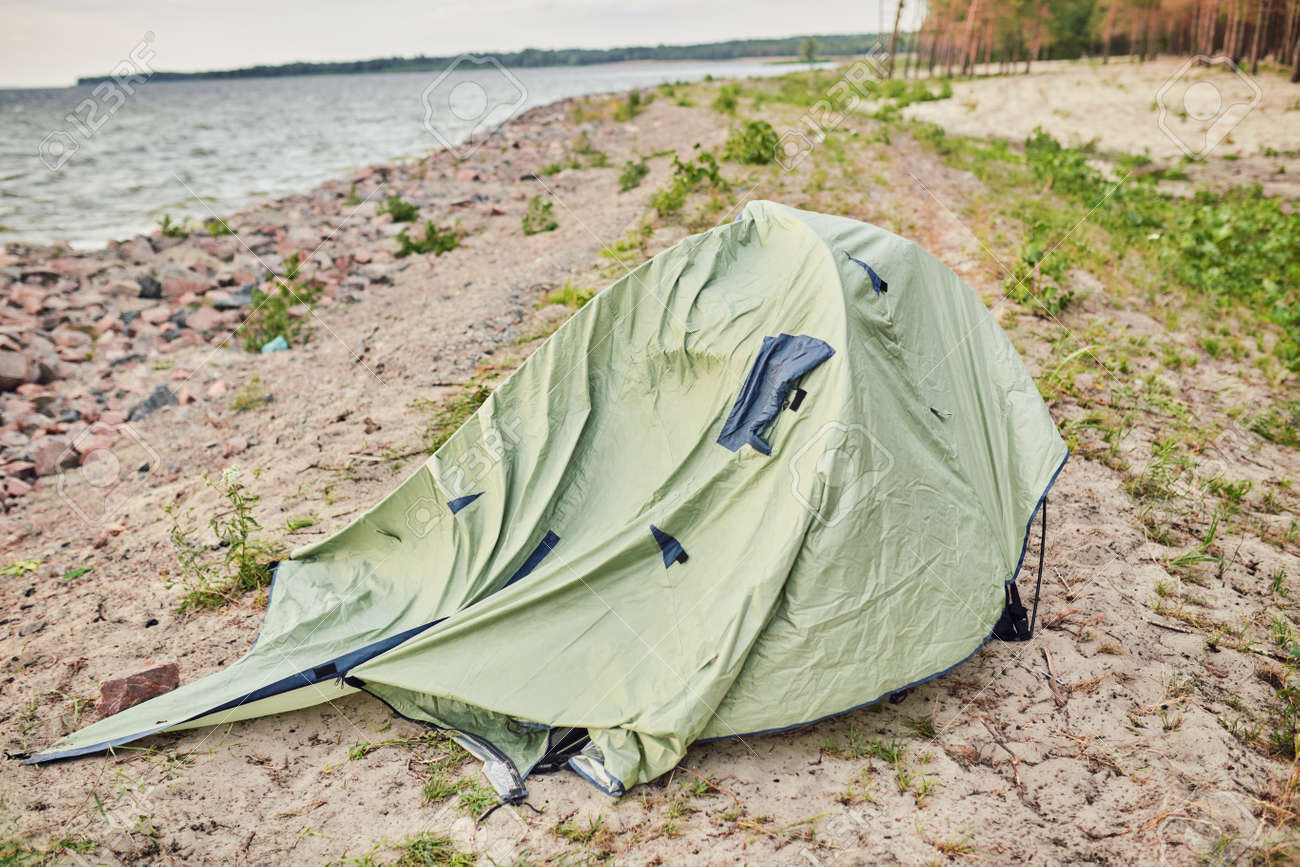 blue broken camping tent on the beach at the stormy weather and good tent at back - 169020533