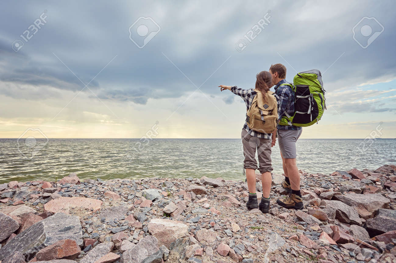 adventure, travel, tourism, hike and people concept - smiling couple with backpacks outdoors - 170687723