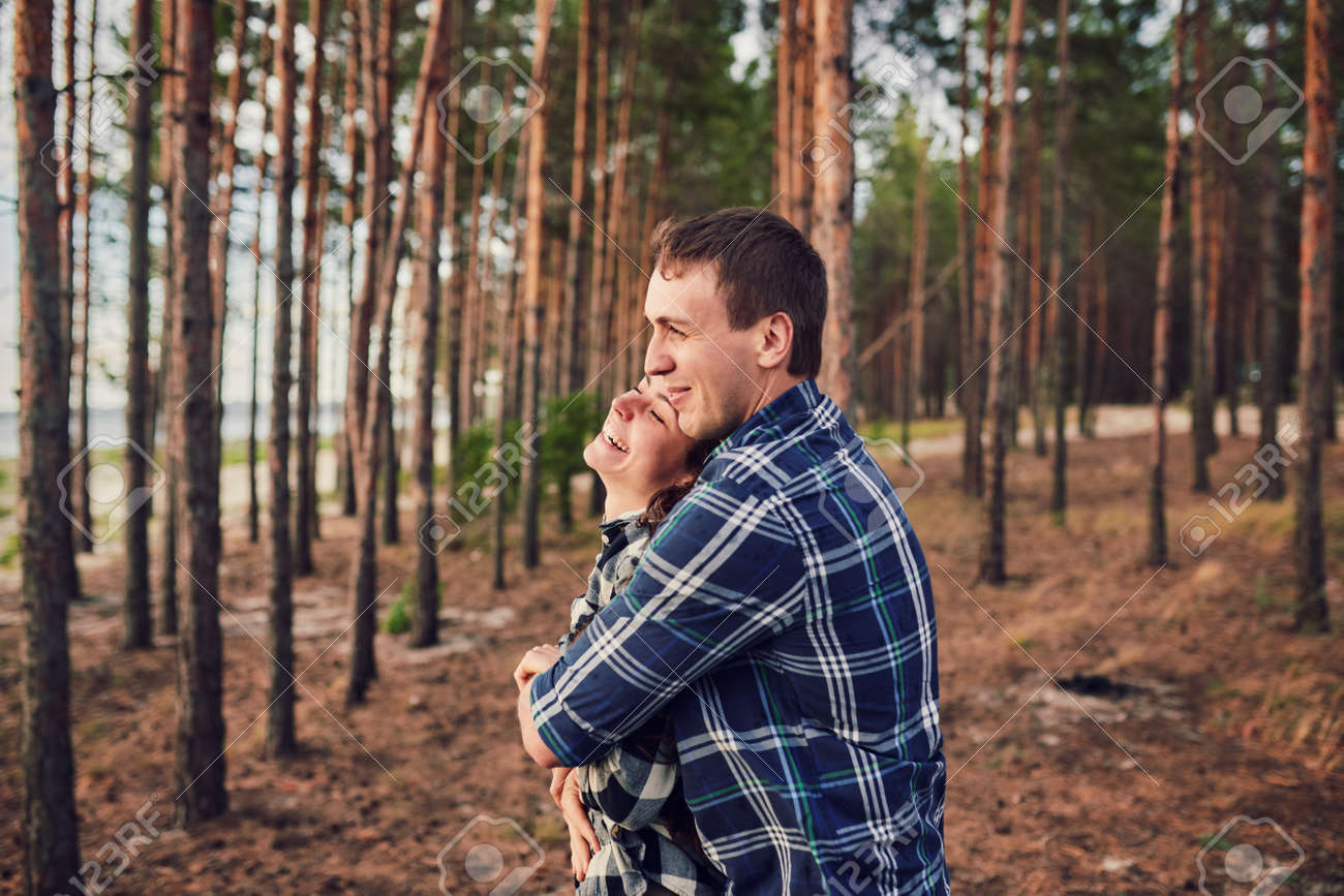 young couple smiling at each other during a romantic date in the forest - strong sunlight - shot against sun - 170687699