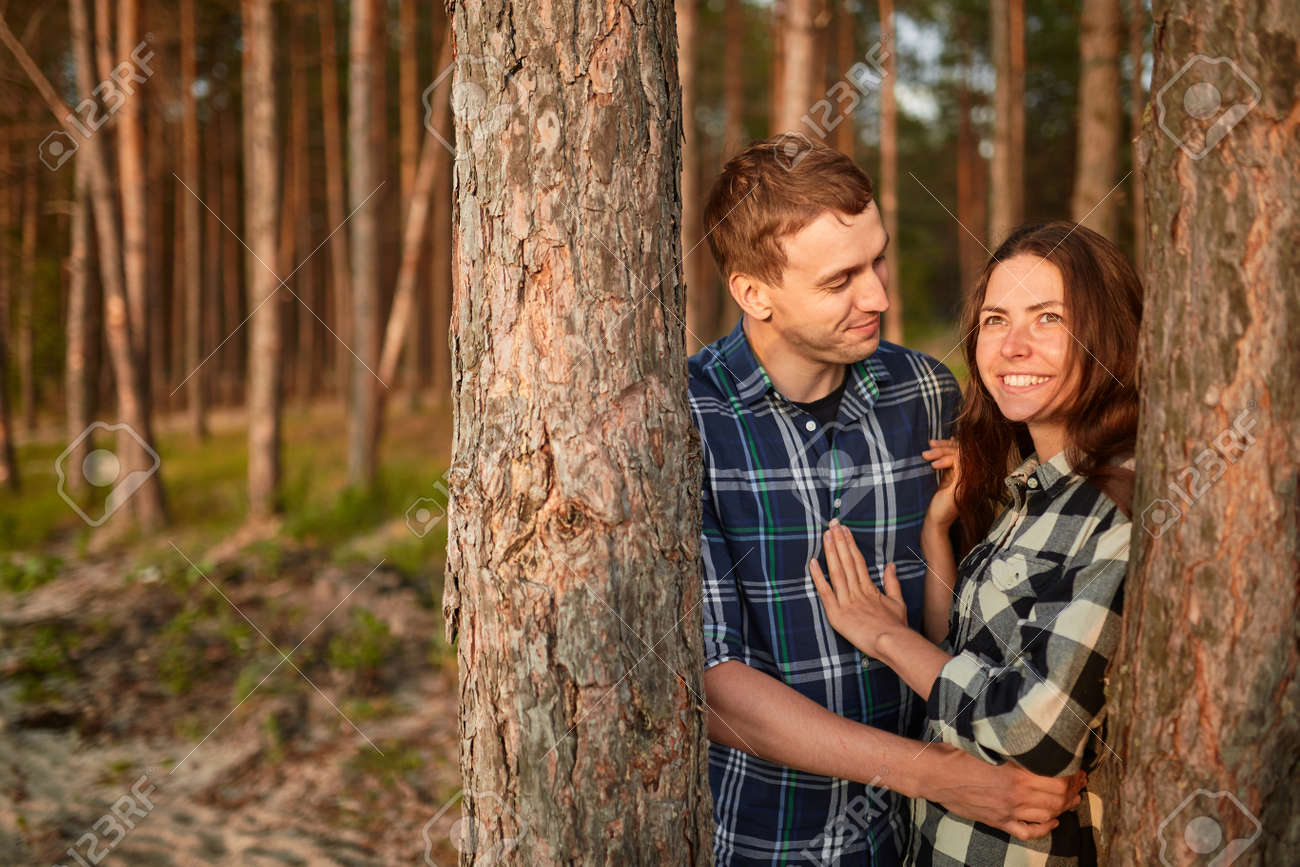 young couple smiling at each other during a romantic date in the forest - strong sunlight - shot against sun - 170687703