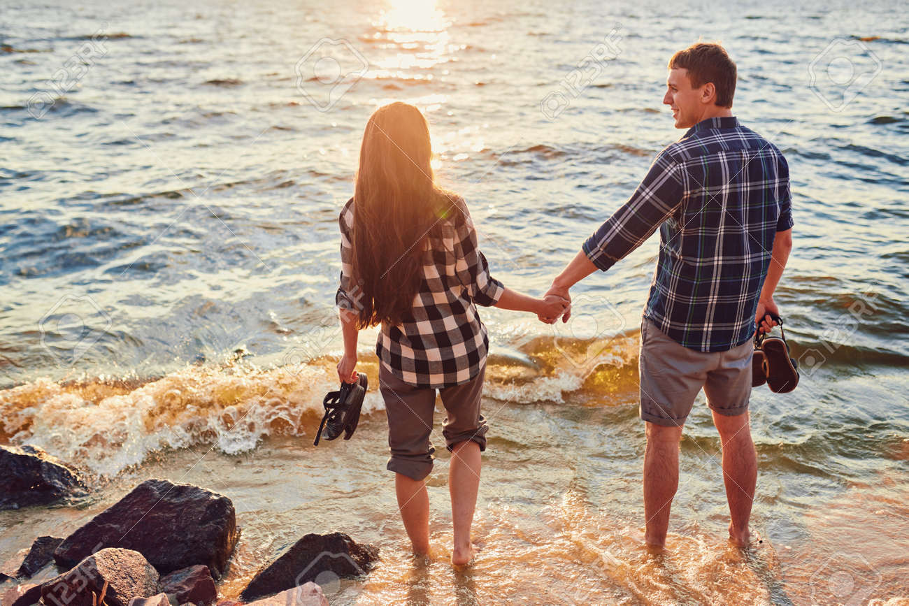 Happy caucasian fashionable couple in love holding hands and walking on coast near river. In background is sunset. - 170687675