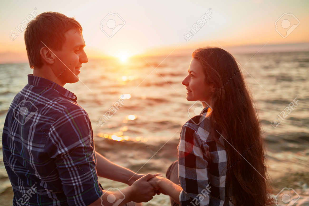 A loving couple is having fun and hugging on the empty sandy sea beach at sunset.They are looking each other and happily smiling. - 170687611