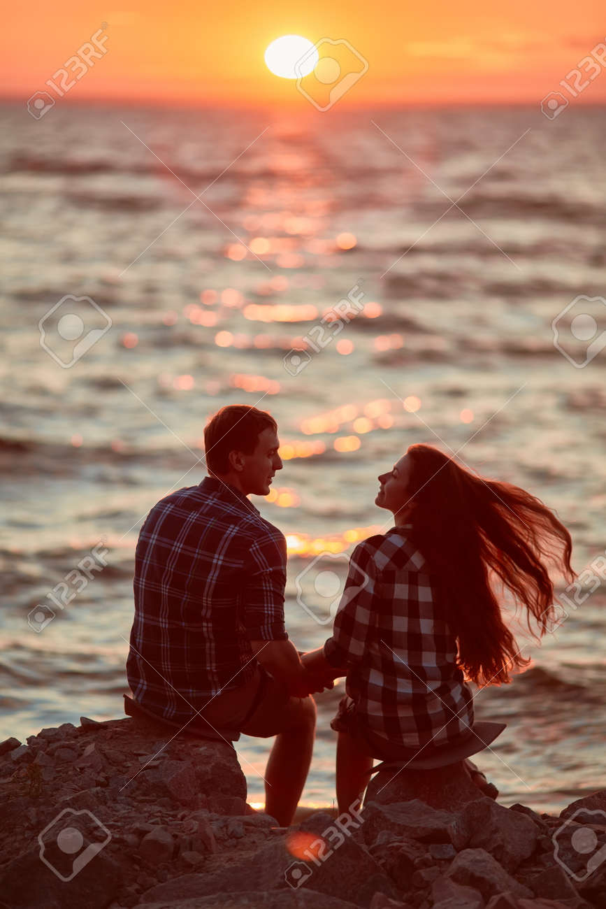 Young couple silhouette on a sea beach on sunset background - 170687615