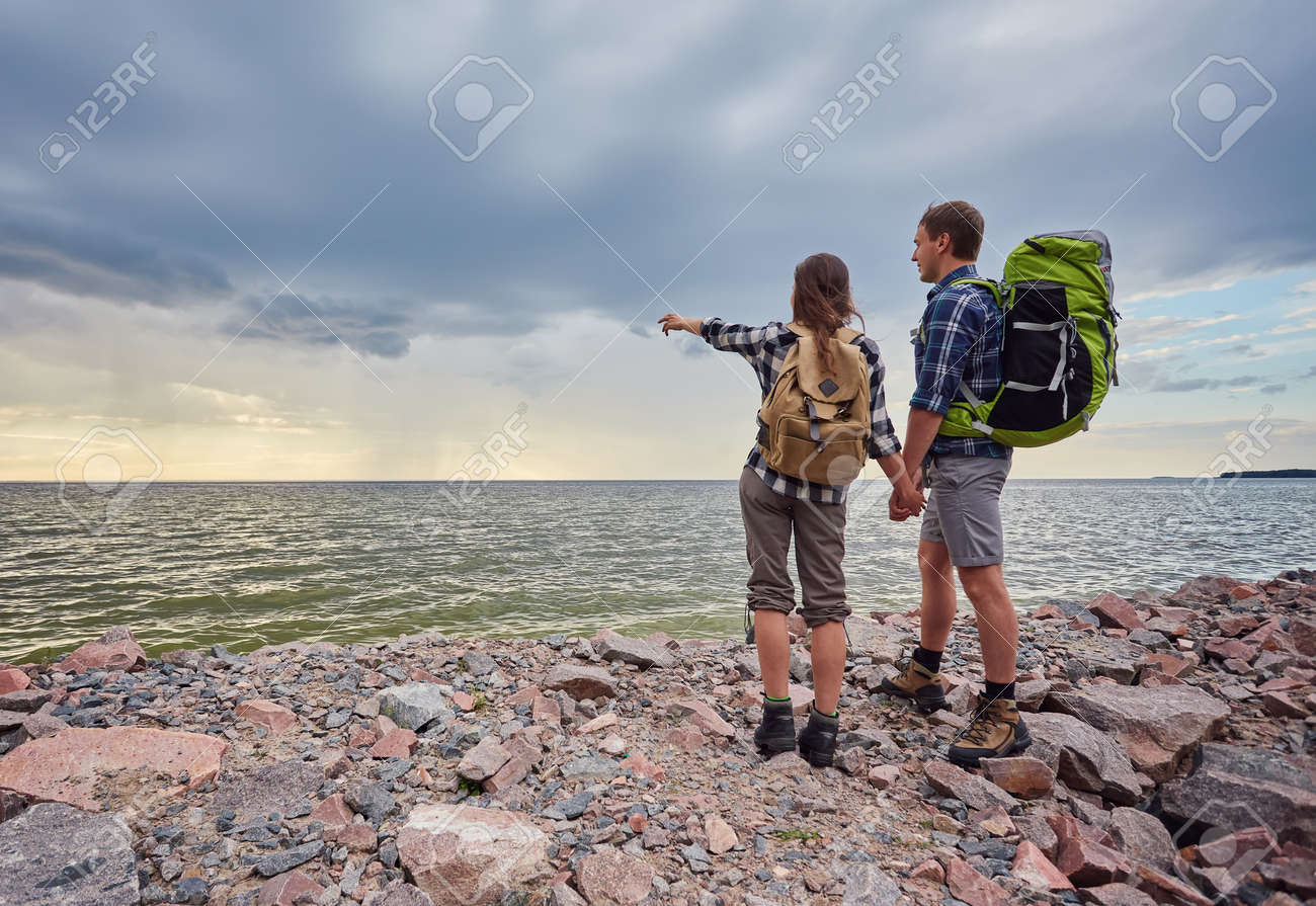 adventure, travel, tourism, hike and people concept - smiling couple with backpacks outdoors - 169020918
