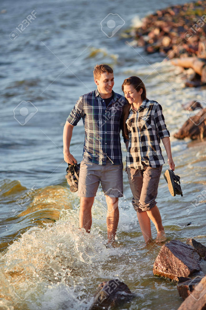 Happy caucasian fashionable couple in love holding hands and walking on coast near river. In background is sunset. - 169020974