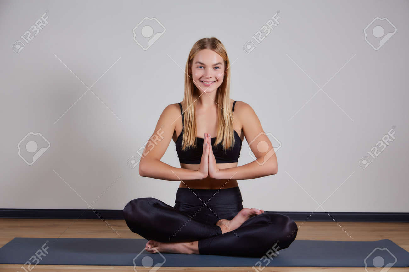 Calm young woman wearing black sportswear practicing yoga, doing Padmasana exercise, sitting in Lotus pose on mat, namaste hands, girl working out at home or in yoga studio with gray walls - 169021091