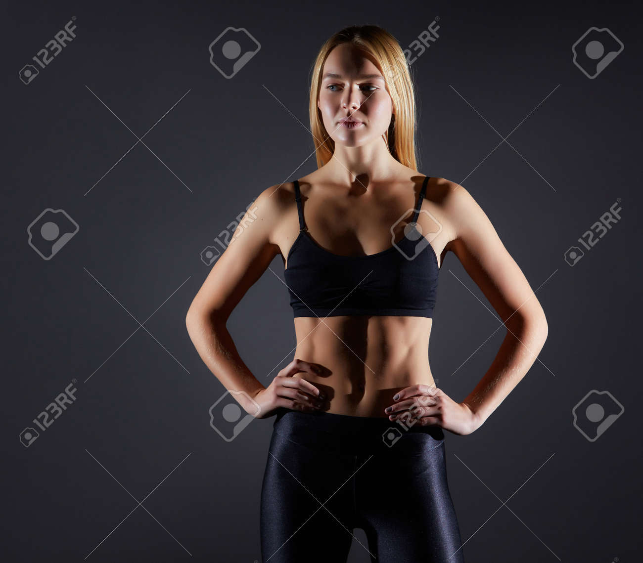 Sportive blonde girl on the background of the black wall of the gym. Body relief and hair sweep - 169021116
