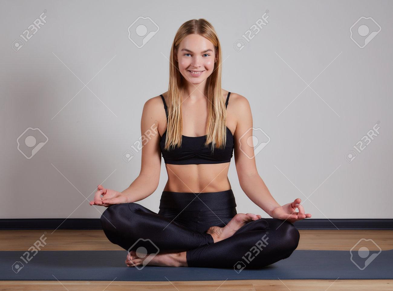 Young woman practicing lotus asana in yoga studio. Padmasana pose - 169021125