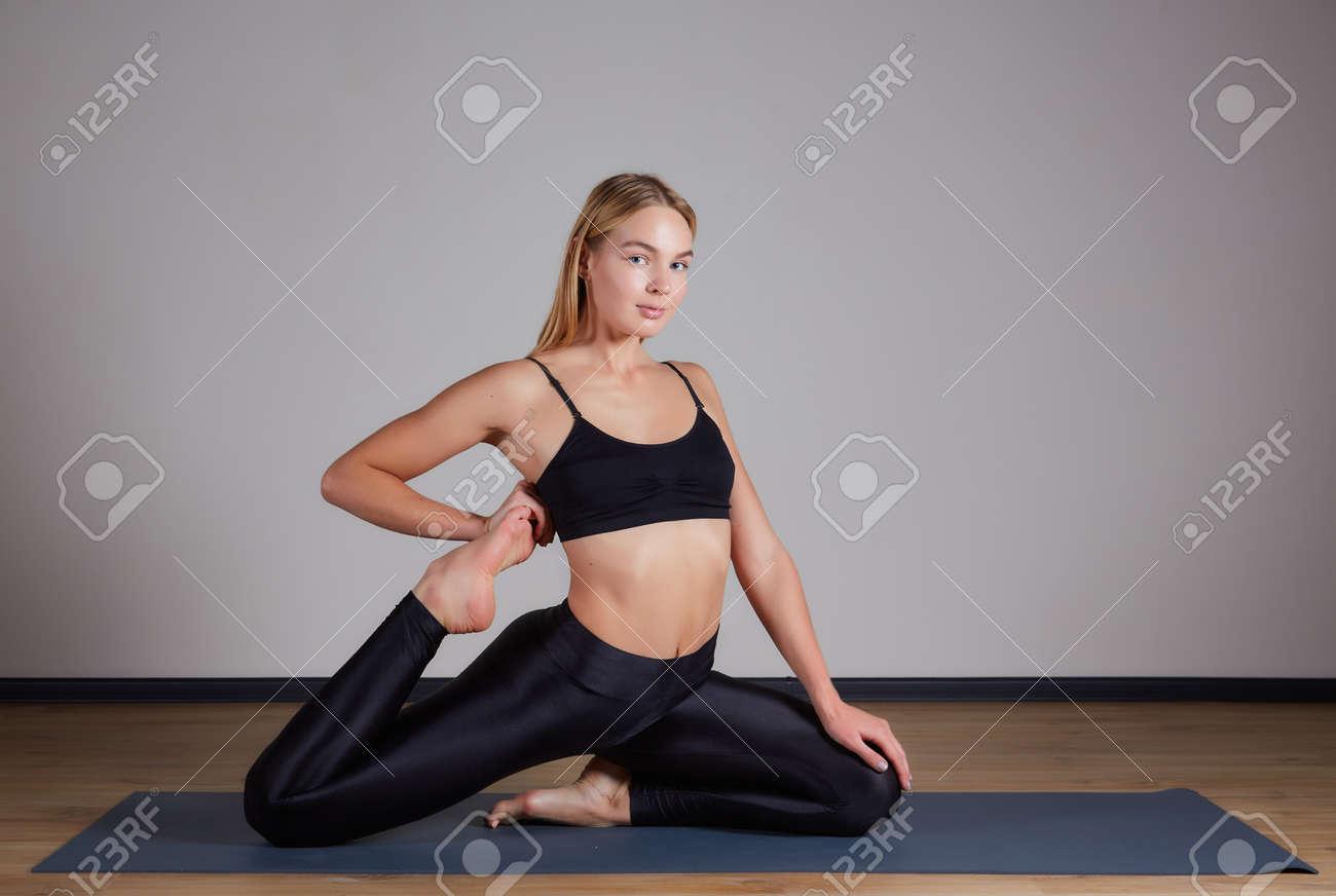 Young yogi woman practicing yoga concept, doing One Legged King Pigeon exercise, Eka Pada Rajakapotasana pose. Working out, wearing sportswear bra and pants, silhouette, loft studio background - 169021129