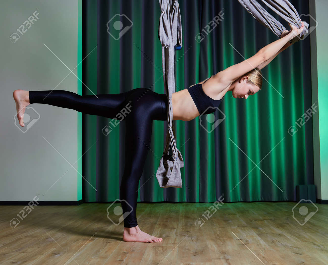 Attractive peaceful young woman doing aerial yoga in studio - 169021165