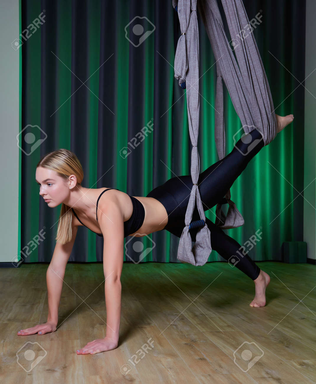 young woman making antigravity yoga exercises in modern gym - 169021181