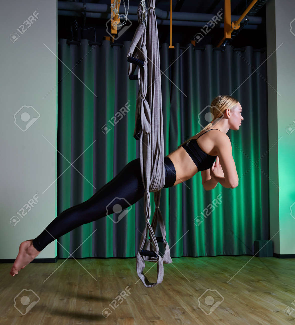young woman making antigravity yoga exercises in modern gym - 169021202