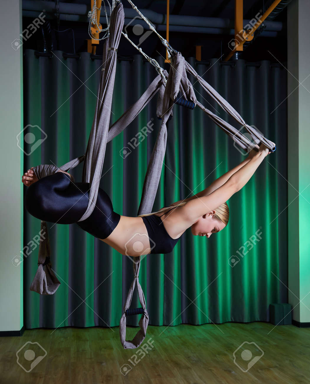 young woman making antigravity yoga exercises in modern gym - 169021259