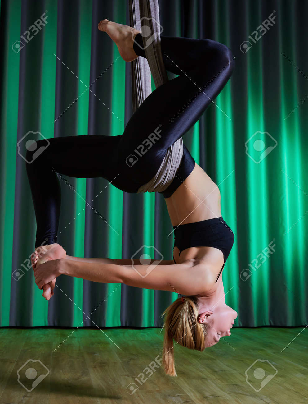 young woman making antigravity yoga exercises in modern gym - 169021293