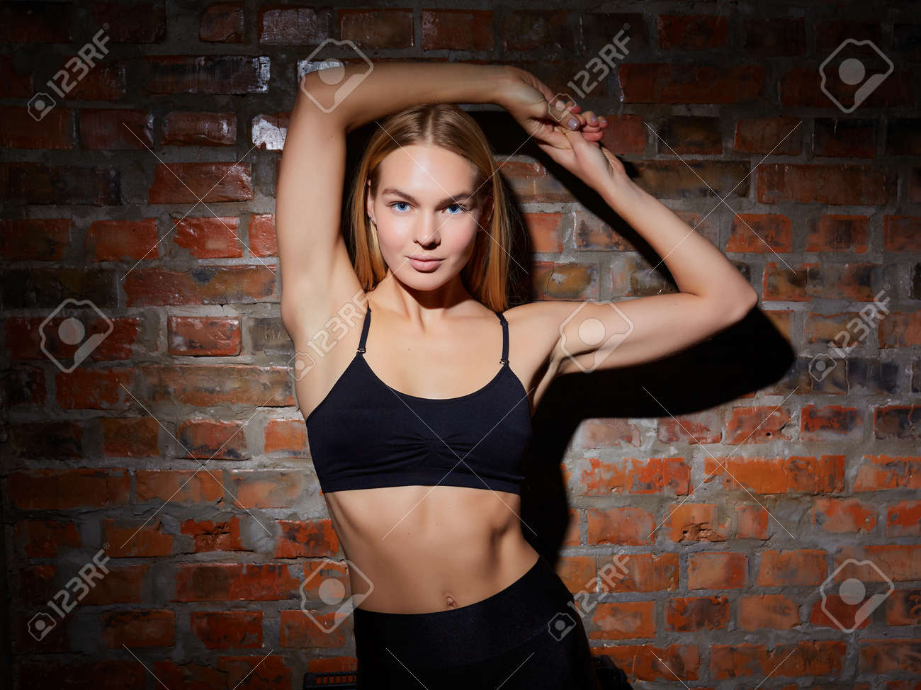 sport and yoga lifestyle concept. Young fit pretty woman dressed in sport clothes poses against brick wall. - 169021298
