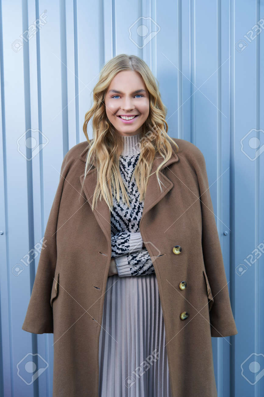 Stylish cute young blonde woman in seasonal fashionable beige coat posing near silver metal wall outdoors. Fashionable girl model in the city. - 169021377